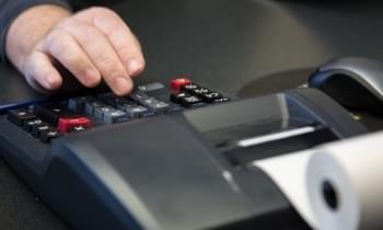 Photo of accountant's hand on adding machine